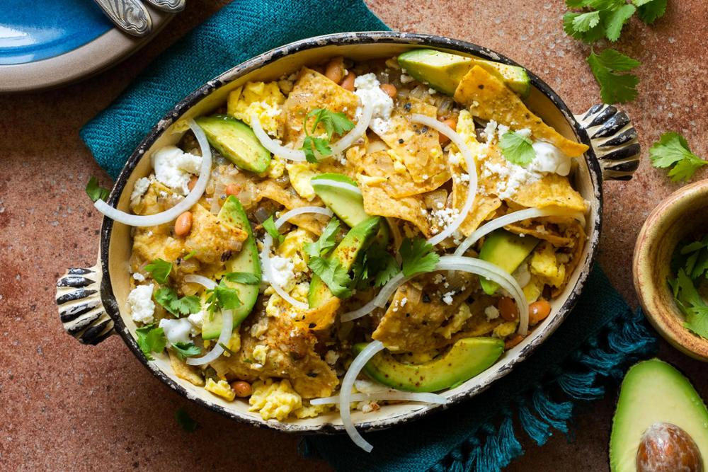 Chilaquiles verdes with soft-scrambled eggs, avocado, and queso fresco